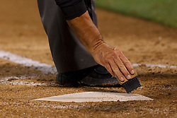 June 28, 2011; Oakland, CA, USA; MLB umpire Phil Cuzzi (10) brushes off home plate during the fifth inning between the Oakland Athletics and the Florida Marlins at the O.co Coliseum.