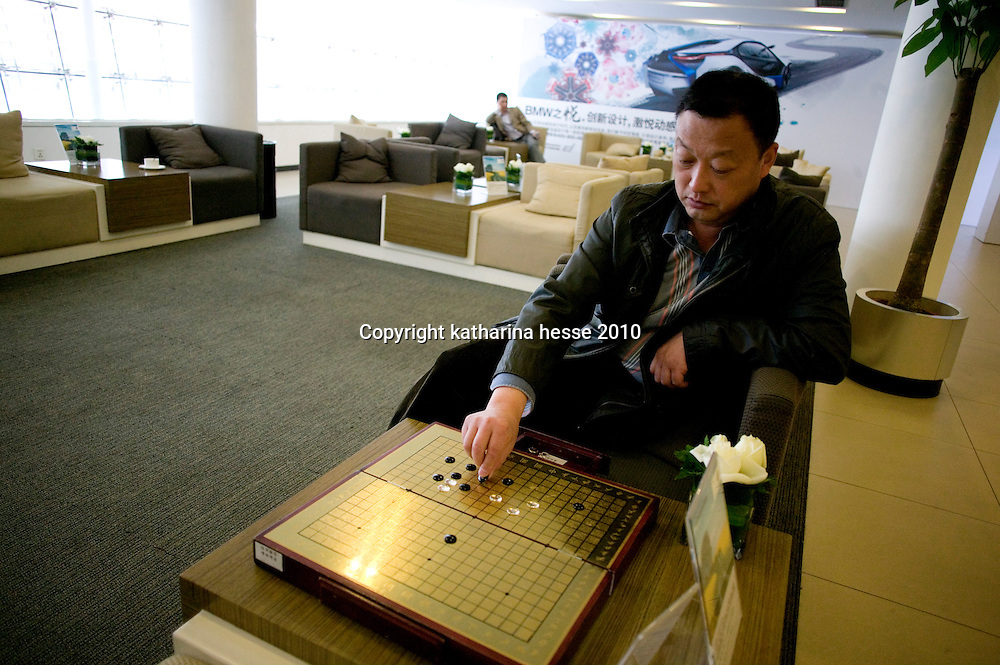 BEIJING, APRIL-22, 2010:  a customers plays Chinese chess while waiting for his car at the BMW dealership .