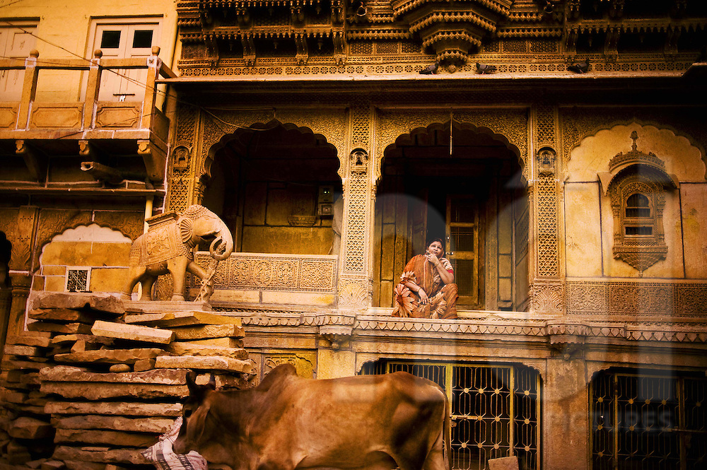 A woman contemplatively sits in front of an ornate building in Rajasthan, India, Asia
