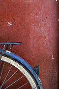 A blue bike rest against a weathered red wall, Hanoi, Vietnam.  Photo by Stan Olszewski/SOSKIphoto