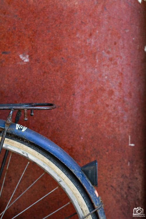 A blue bike rest against a weathered red wall, Hanoi, Vietnam.  Photo by Stan Olszewski/SOSKIphoto