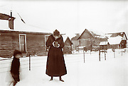 Vintage photo: woman taking a photo with a box camera in the snow at a farm, circa 1910 Barn, fence and boy.