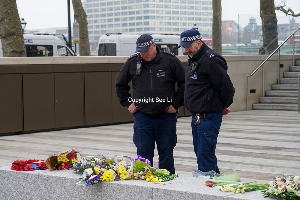 Police looking at the Flower tributes for the victims of terror attacks at New Scotland Yard,London,UK