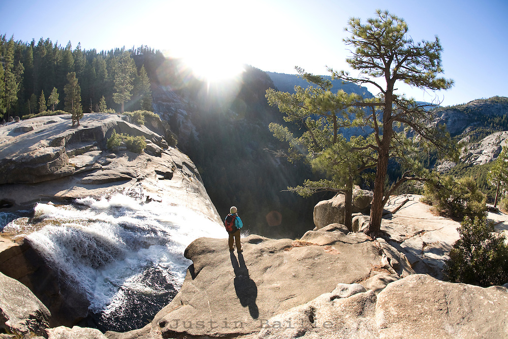 Woman looking over Nevada Falls while backpacking along the John Muir Trail in Yosemite National Park, Ca.