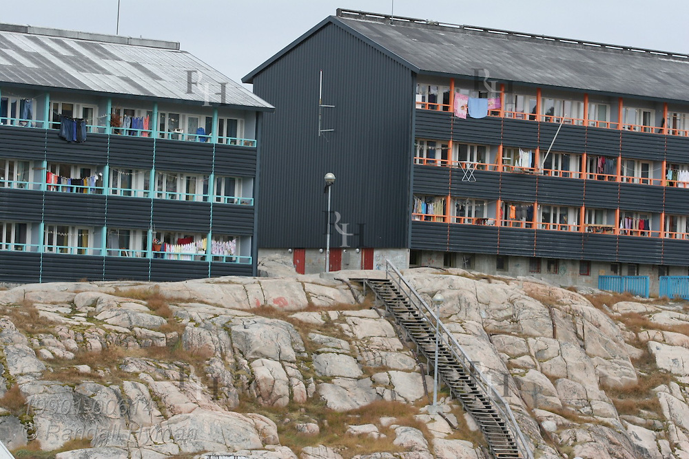 Modern apartment buildings perch atop rocky slope in Ilulissat, third largest town in Greenland.