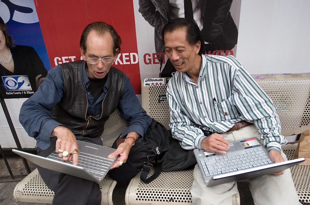 Two men have fun with their Apple laptops in Chinatown, Manhattan, NY, USA.