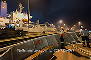 Workers secure lines on the bow of a ship as it transits the Panama Canal at nighttime.