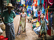 14 JUNE 2013 -  PATHEIN, AYEYARWADY, MYANMAR: A woman walks down an aisle in the market in Pathein. Pathein, sometimes also called Bassein, is a port city and the capital of the Ayeyarwady Region, Burma. It lies on the Pathein River (Bassein), which is a western branch of the Irrawaddy River. It's the fourth largest city in Myanmar (Burma) about 190 km west of Yangon.   PHOTO BY JACK KURTZ