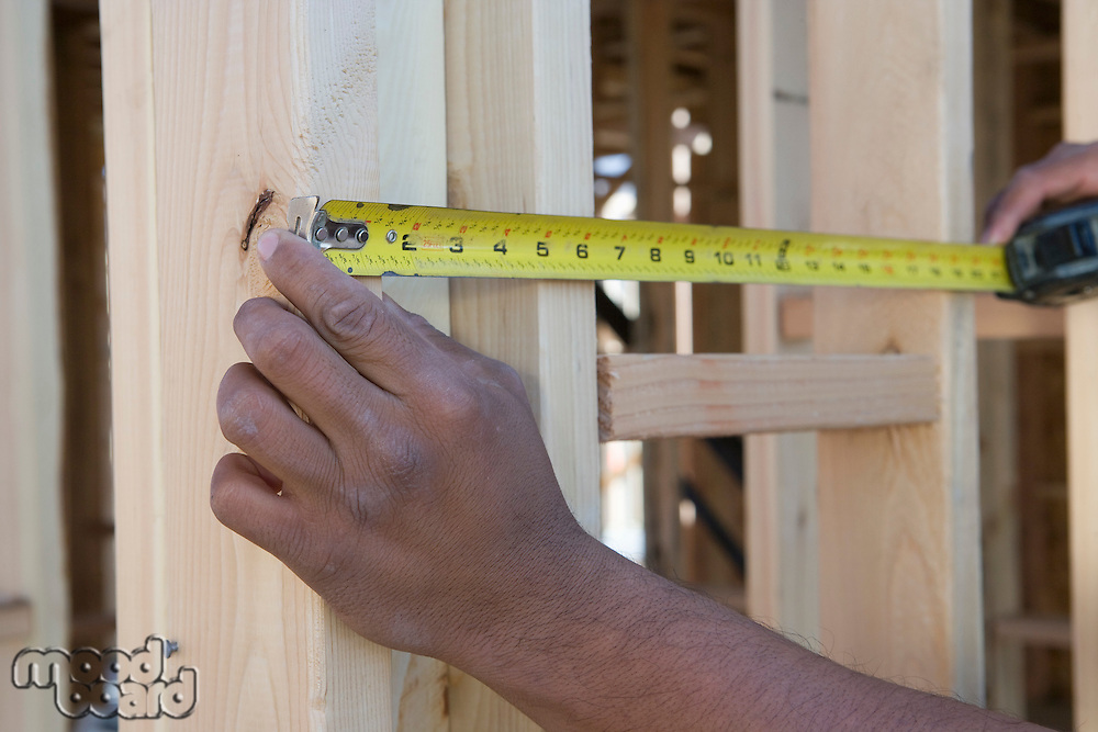 Person measuring half constructed wall with tape measure