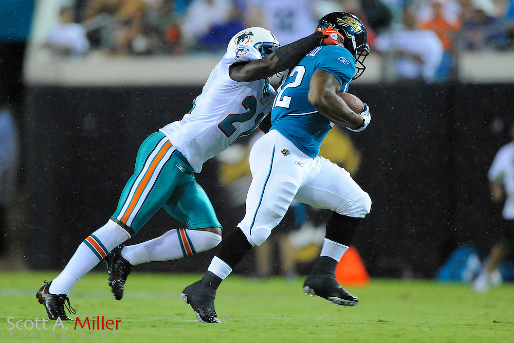 Aug. 21, 2010; Jacksonville, FL, USA; Jacksonville Jaguars running back Maurice Jones-Drew (32) is tackled by Miami Dolphins cornerback Vontae Davis (21) during their game at EverBank Field. ©2010 Scott A. Miller