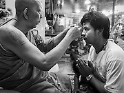 "07 MARCH 2015 - NAKHON CHAI SI, NAKHON PATHOM, THAILAND:  A monk blesses a man by rubbing gold leaf on the man's forehead at the Wat Bang Phra tattoo festival. Wat Bang Phra is the best known ""Sak Yant"" tattoo temple in Thailand. It's located in Nakhon Pathom province, about 40 miles from Bangkok. The tattoos are given with hollow stainless steel needles and are thought to possess magical powers of protection. The tattoos, which are given by Buddhist monks, are popular with soldiers, policeman and gangsters, people who generally live in harm's way. The tattoo must be activated to remain powerful and the annual Wai Khru Ceremony (tattoo festival) at the temple draws thousands of devotees who come to the temple to activate or renew the tattoos. People go into trance like states and then assume the personality of their tattoo, so people with tiger tattoos assume the personality of a tiger, people with monkey tattoos take on the personality of a monkey and so on. In recent years the tattoo festival has become popular with tourists who make the trip to Nakorn Pathom province to see a side of ""exotic"" Thailand.   PHOTO BY JACK KURTZ"