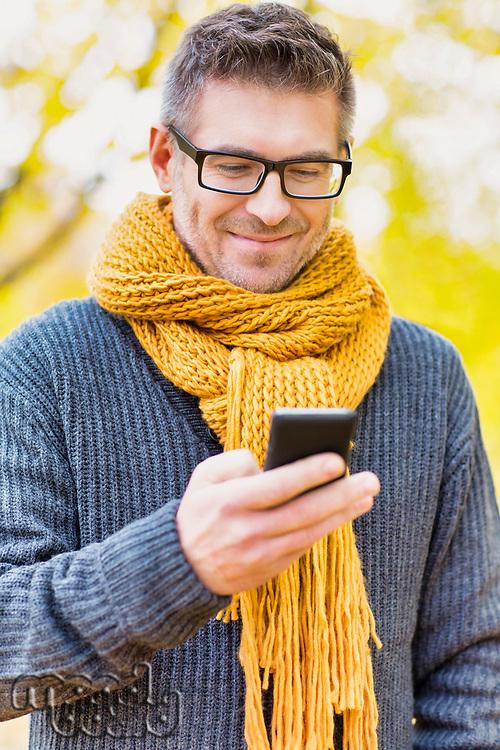 Portrait of mature attractive man using smartphone under maple tree in park