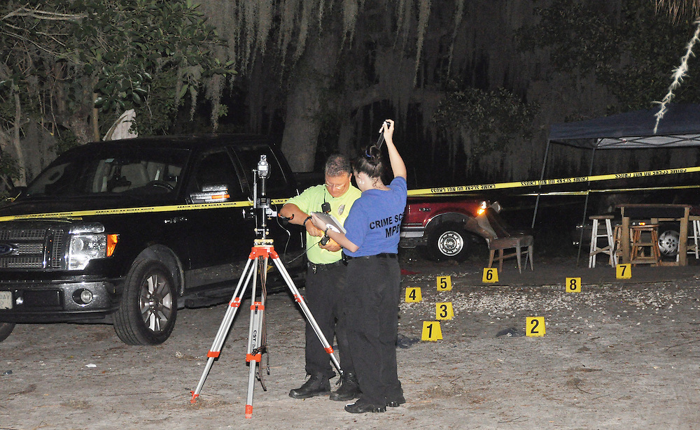 Andrew Knapp, FLORIDA TODAY -- July 21, 2011 -- Crime scene investigators collect measurements at the scene of a shooting Thursday evening between Hopkins and Line streets in south Melbourne.