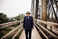 A railway security guard stands for a portrait at a small town along the Red River in northern vietnam.