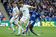 Leicester City forward Jeff Schlupp tackles Swansea City defender Federico Fernandez during the Barclays Premier League match between Leicester City and Swansea City at the King Power Stadium, Leicester, England on 24 April 2016. Photo by Alan Franklin.