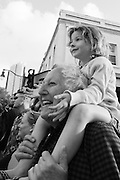 A young girl sits on the shoulders of an older man watching a parade in downtown Honolulu, Hawaii. Missoula Photographer