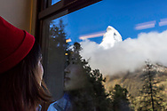 A young woman admiring in awe, and reverence, the view of the Matterhorn revealing itself from the clouds from the train up the mountain. The reflection of her face in the window of the train reveals her reverence.