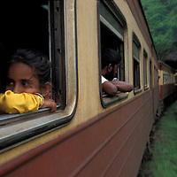 Sri Lanka, Young girl peers from window on train toward Kandy