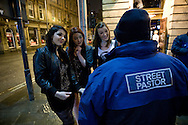 Members of the the Derby Street Pastor team talking to local people outside a bar while on patrol in Derby city centre. Street Pastor was pioneered in London in January 2003 and Derby Street Pastors is a partnership of 25 local churches, Derbyshire Police, local council and various groups concerned with city centre street business and safety. Each Street Pastor team member works a minimum of one night a month, usually from 10pm to around 4am.
