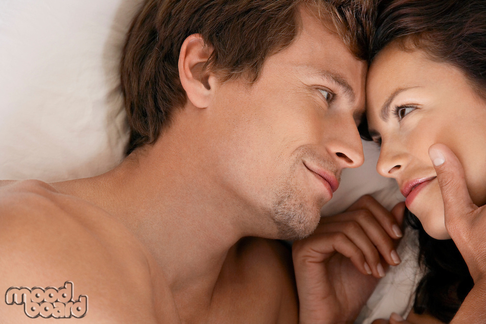 Couple embracing lying down head and shoulders close up