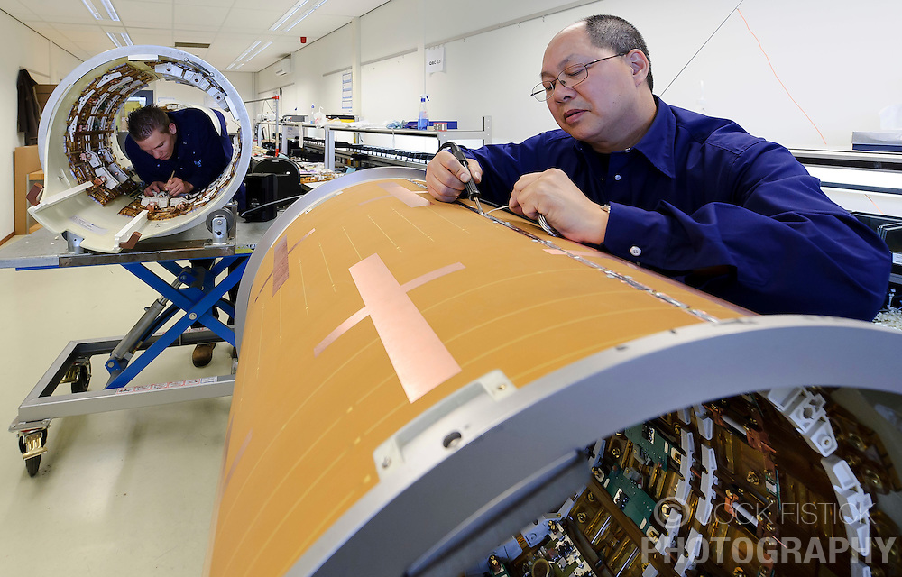 Engineer FW Choy, right, works on the gradient coil while engineer Dave Lemmens, works on a body coil of an MR scanner, at the Philips Healthcare production facility, in Best, the Netherlands, on Tuesday, Oct. 12, 2010. (Photo © Jock Fistick)