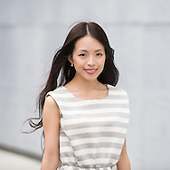 Portrait of a young Japanese woman as she walks through stree.