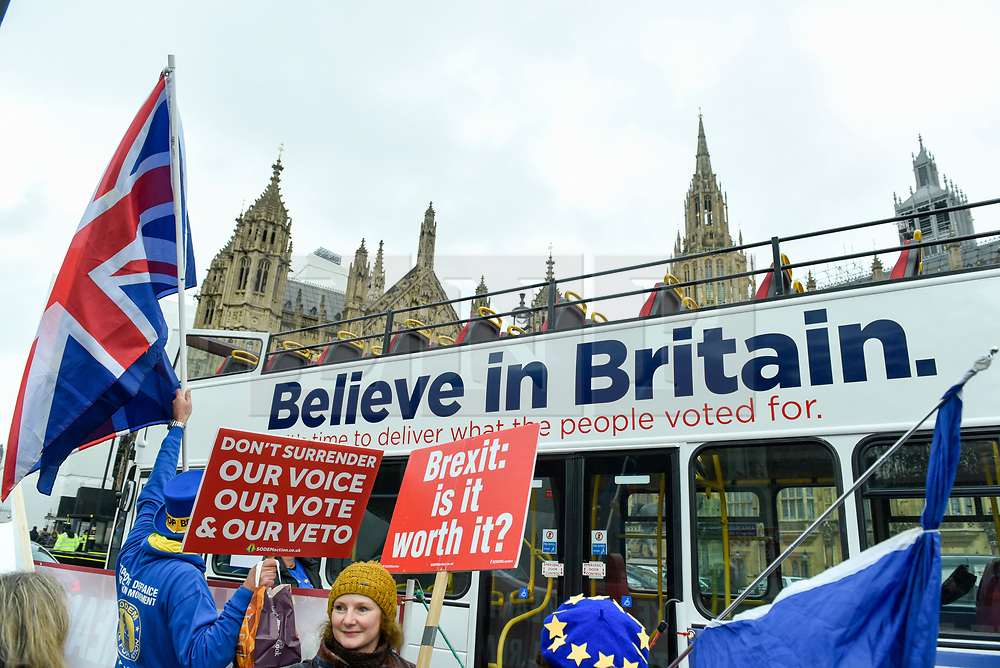 © Licensed to London News Pictures. 05/12/2018. LONDON, UK.  Anti-Brexit supporters demonstrate outside the Houses of Parliament as a bus decorated by the Leave Means Leave campaign passes by.  MPs are debating Theresa May's Brexit deal with the European Union ahead of the meaningful vote of December 11.  Photo credit: Stephen Chung/LNP
