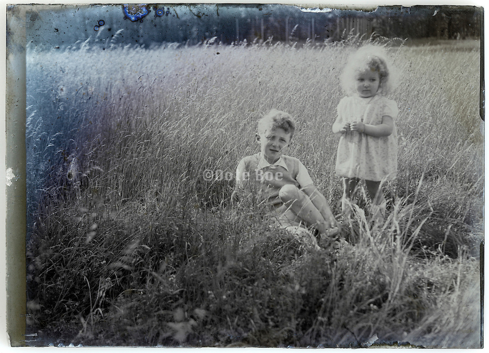 eroding 1900s glass plate with two little children in field