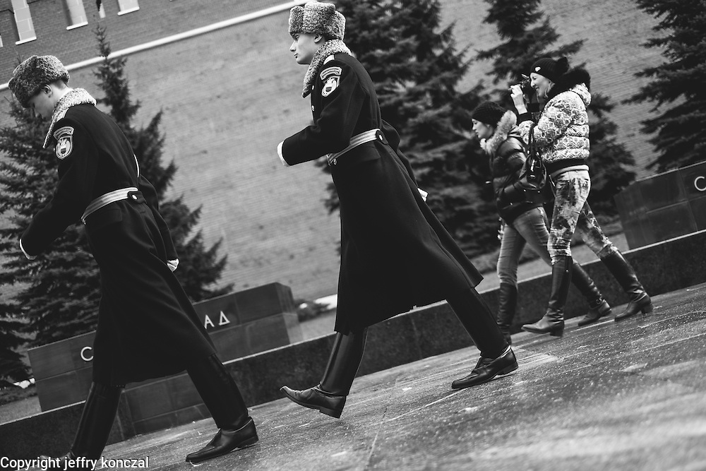 Women walk in-step with Russian military members outside of the Kremlin in Moscow, Russia.