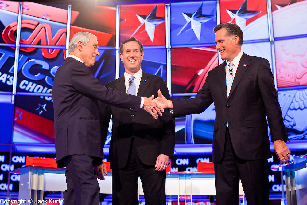"""22 FEBRUARY 2012 - MESA, AZ:  Congressman RON PAUL (left) shakes hands with Senator RICK SANTORUM and Governor MITT ROMNEY at the Arizona Republican Presidential Debate in the Mesa Arts Center in Mesa, AZ, Wednesday. It is the last debate before the Michigan and Arizona Republican primaries on Feb. 28 and """"Super Tuesday"""" on March 6. PHOTO BY JACK KURTZ"""