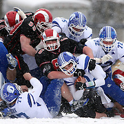 Quarterback Silas Wyper, Darien, is tackled by the New Canaan defense during the New Canaan Rams Vs Darien Blue Wave, CIAC Football Championship Class L Final at Boyle Stadium, Stamford. The New Canaan Rams won the match in snowy conditions 44-12. Stamford,  Connecticut, USA. 14th December 2013. Photo Tim Clayton