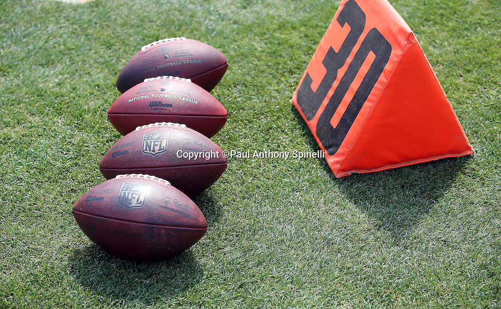 Four NFL footballs lie on the grass next to the 30 yard line marker before the Oakland Raiders 2015 NFL week 1 regular season football game against the Cincinnati Bengals on Sunday, Sept. 13, 2015 in Oakland, Calif. The Bengals won the game 33-13. (©Paul Anthony Spinelli)