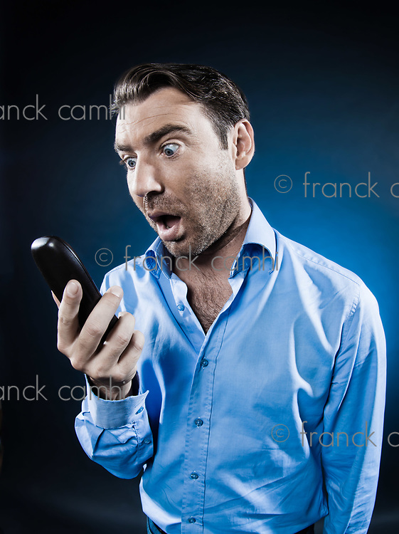 caucasian man looking at phone surprised unshaven portrait isolated studio on black background
