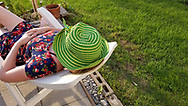 A woman with a bright green hat naps on a plastic chair, Consecon, Canada