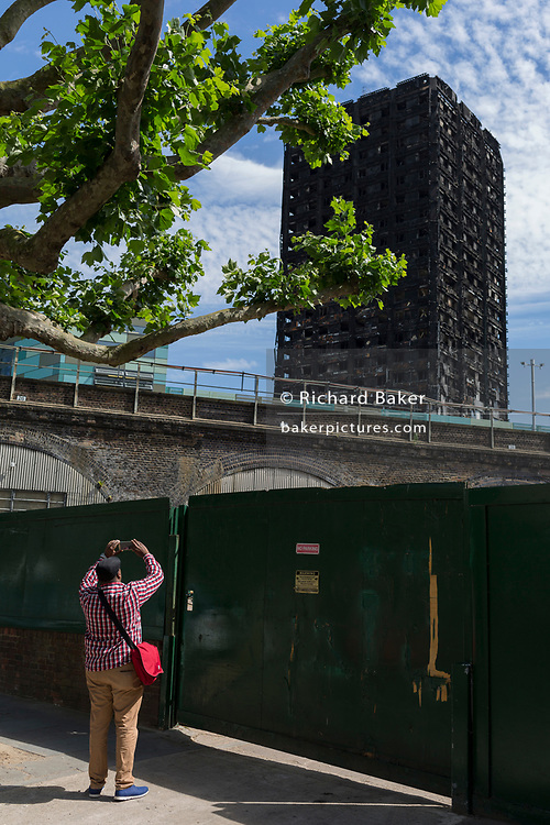 Twelve days after the devastating fire that killed an unspecified number of people in Grenfell Tower, a passer-by pauses to take a picture of the charred and blackened tower block which remains a crime scene, on 26th June 2017, in the London borough of Kensington & Chelsea, England.