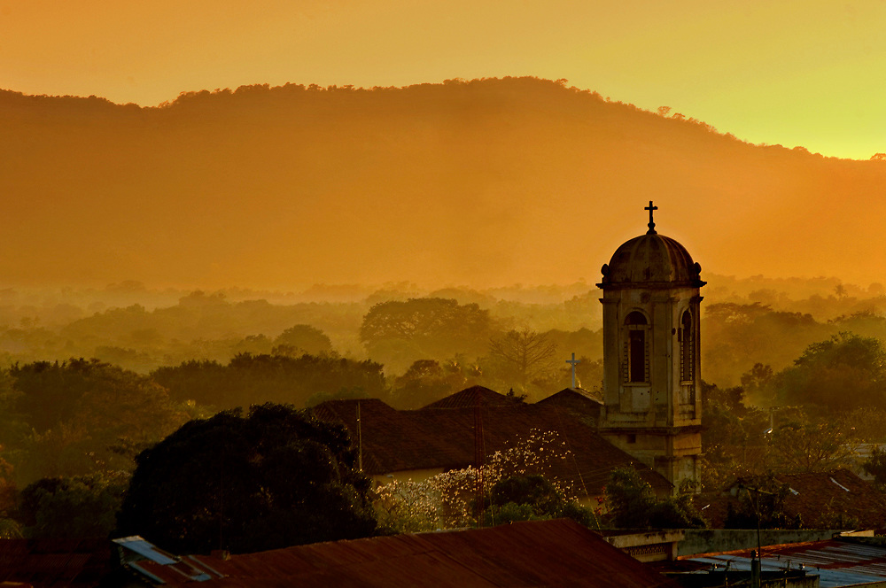 Church steeple rises over the landscape of Leon, Nicaragua at sunset.