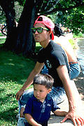 Father and son age 27 and 4 resting during walk around Lake Nokomis.  Minneapolis Minnesota USA