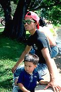 Father and son age 27 and 4 resting during walk around Lake Nokomis.  Minneapolis Minnesota USA