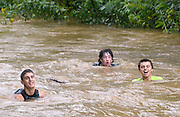 David Rugemer (middle) and his buddies, Abraham Ramos (left) and Tyler Hartman, all of Patapsco, MD, are having a wild swim riding the flood waters of the Patapsco River following Thursday's heavy rains.