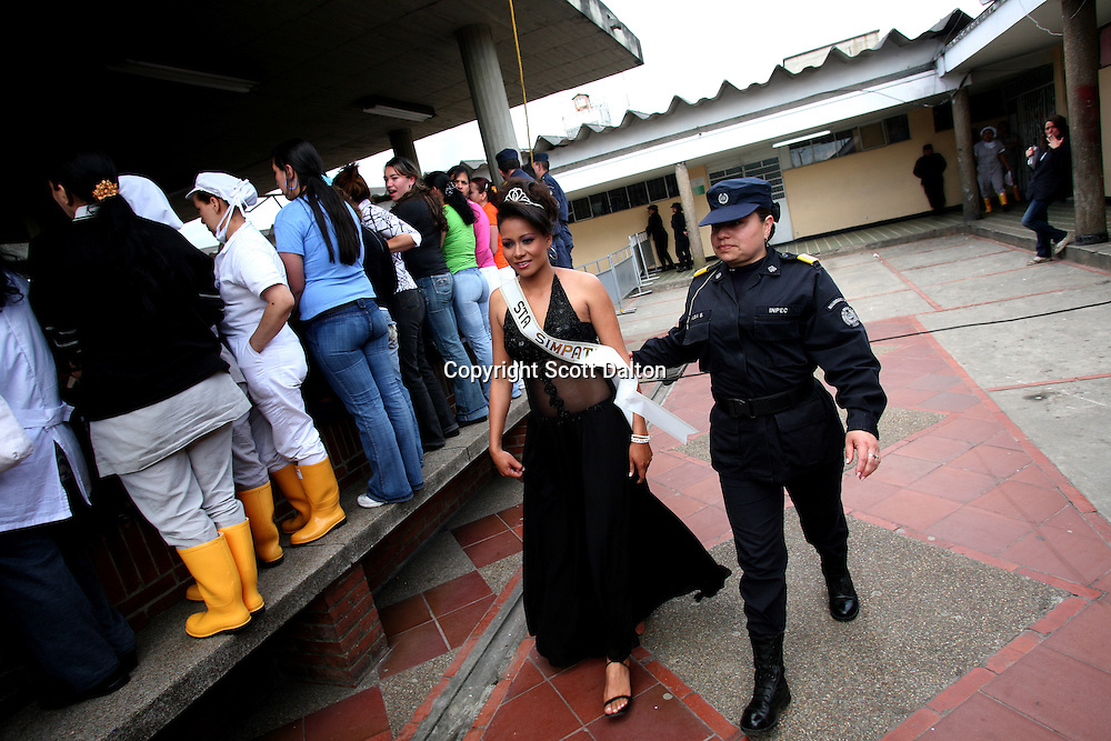 Claudia Patricia Moncada, 29, the reigning prison beauty queen, serving time for money laundering and drug trafficking, is escorted by a guard to the beauty pageant at the Good Shepard Prison, a female prison, in Bogotá, Colombia on Friday, September 21, 2007. Each September, the female inmates of the Good Shepherd Prison hold a beauty pageant in honor of the Virgin of Mercedes, the patron saint of prisoners. (Photo/Scott Dalton).