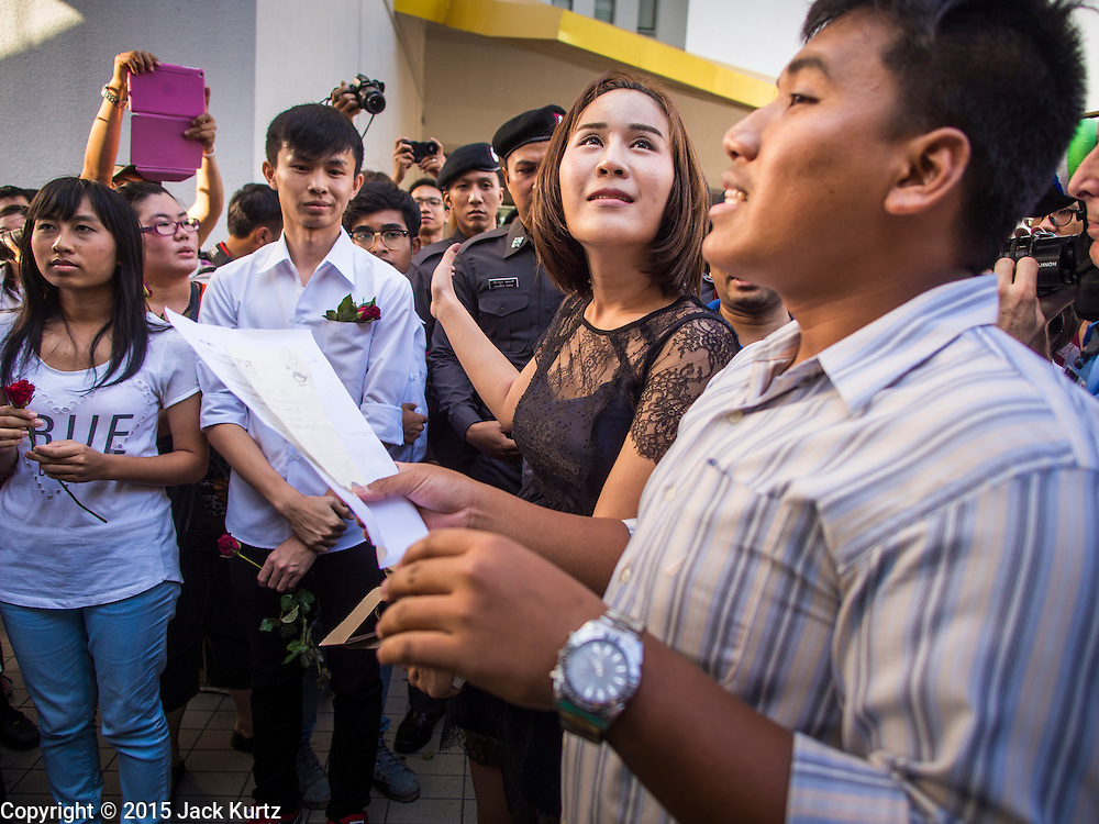 "14 FEBRUARY 2015 - BANGKOK, THAILAND: NATCHACAH KONG-UDOM, center, a Thai democracy advocate, and other protestors, participate in a chant during a protest against the military coup. Dozens of people gathered in front of the Bangkok Art and Culture Centre in Bangkok Saturday to hand out red roses and copies of George Orwell's ""1984."" Protestors said they didn't support either Red Shirts or Yellow Shirts but wanted a return of democracy in Thailand. The protest was the largest protest since June 2014, against the military government of General Prayuth Chan-Ocha, who staged the coup against the elected government. Police made several arrests Saturday afternoon but the protest was not violent.    PHOTO BY JACK KURTZ"