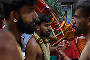 Men carrying arched wooden frames with peacock feathers, called kavadi, in the parade celebrating the festival of Ganesh Chaturthi, marking the birth of the Hindu god Ganesha, on the streets of the La Chapelle area of the 18th arrondissement of Paris, France, on Sunday 1st September 2019. The annual religious festivities and parade take place near the Ganesha Temple of Paris, or Sri Manicka Vinayakar Alayam Temple, the largest Hindu temple in France. Ganesha is the elephant-headed Hindu God of Beginnings, son of Shiva and Parvati, who represents love and knowledge. Picture by Manuel Cohen