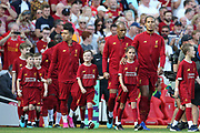 Happy mascots as they come out onto the Anfield pitch with Liverpool defender Virgil van Dijk (4) Liverpool midfielder Fabinho (3) Liverpool forward Roberto Firmino (9) and Liverpool forward Sadio Mane (10) during the Premier League match between Liverpool and Arsenal at Anfield, Liverpool, England on 24 August 2019.