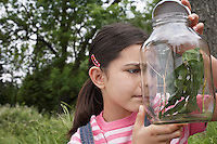 Girl (7-9) examining jar of stick insects outdoors