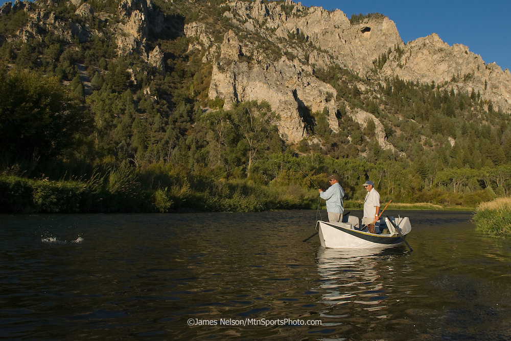 A fly fisherman brings a trout to the boat on the South Fork of the Snake River, Idaho.