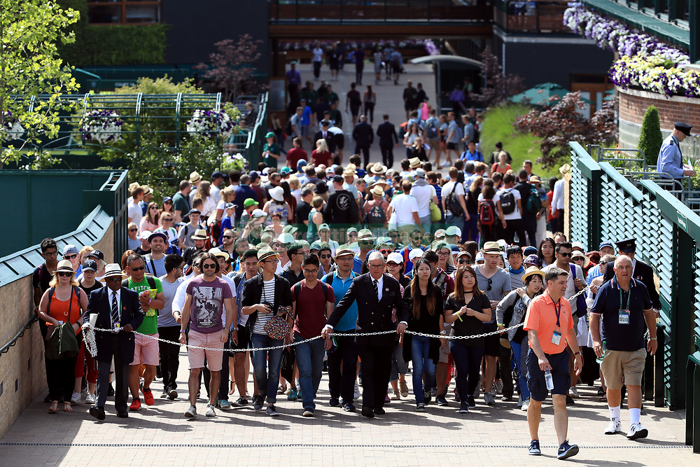 Spectators are led into the grounds by stewards at the start of day two of the Wimbledon Championships at The All England Lawn Tennis and Croquet Club, Wimbledon.