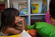 Diully Stefane Zanoni listening to a story in the community library, Biblioteca Comunitaria do Arquipelago, Porte Alegre, Brazil. <br /> <br /> Cirandar is working in partnership with  C&A and C&A Instituto to implement a network of Community Libraries in eight communities of Porto Alegre. sits on the floor listening to a story in the community library, Biblioteca Comunitaria do Arquipelago, Porte Alegre, Brazil. <br /> <br /> Cirandar is working in partnership with  C&A and C&A Instituto to implement a network of Community Libraries in eight communities of Porto Alegre.