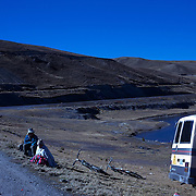 "Mountain Biking on Death Road, Bolivia...Locals watch A tour group of Mountain Bikers prepare at La Cumbre the starting point of the days ride along death road...The North Yugas Road is a 64 Kilometer road leading from La Paz to Corioico. It is legendary for it's extreme danger and in 1995 the Inter American Development Bank christened is as the ""world's most dangerous road"".. The road was built in the 1930's during the Chaco War by Paraguayan prisoners to connect the Amazon rainforest region of Northern Bolivia to it's capital City La Paz. One estimate is that 200 to 300 travelers were killed yearly along the road. On 24 July 1983, a bus veered off the Yungas Road and into a canyon, killing more than 100 passengers in what is said to be Bolivia's worst road accident..A new stretch of the La Paz-Coroico highroad was opened in 2006 to bypass the notorious stretch known as death road..The danger of the road has now made it a popular tourist destination starting in the 1990's and drawing thrill-seekers and mountain bike enthusiasts who ride on the 64km mainly downhill stretch from La Cumbre, a 4,700 meter peak to Yolosa, a decent of 3600 meter's (11,800 feet). The journey includes breathtaking views of snow covered peaks and towering cliffs and starts along modern asphalted road before entering the jungle itself and the most dangerous and notorious part of the ride. The infamous narrow dirt road, most of the road no wider than 3.2 meter's, is cut into the side of the mountain with sheer drops to the left of up to 600 meter's with virtually no safety rails on the winding steep decent..There are now many tour operators catering to this activity, providing information, guides, transport and equipment. Nevertheless, the Yungas Road remains dangerous. At least 13 of these cyclists died on the ride since 1998, the latest A 28-year-old Israeli traveler was killed in April 2010  the group of cyclists arrived at a heavily foggy area. The woman got separated from the group, and"