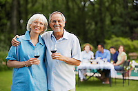 Middle-aged couple in back yard with glasses of wine portrait