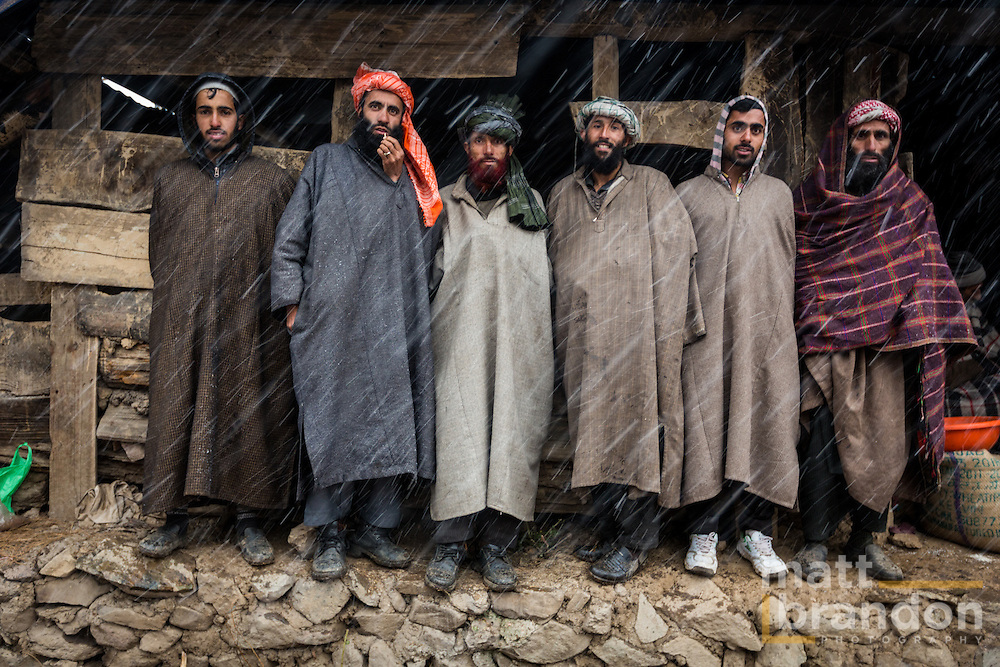 "Six Pahari Gujjar men take refuge from the snow under the eves of a barn. These men wear the Kashmiri, ""pharan"" or woolen poncho to stay warm. Pahalgam, Kashmir, India"